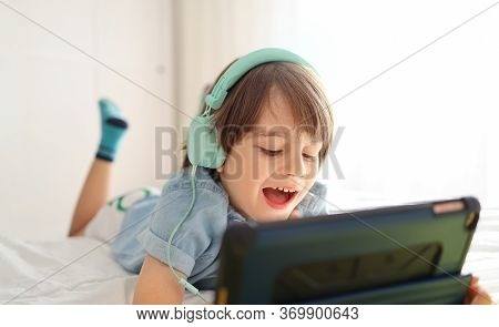 Modern Little Boy In Headphones Is Using A Digital Tablet And Smiling While Lying On His Bed At Home