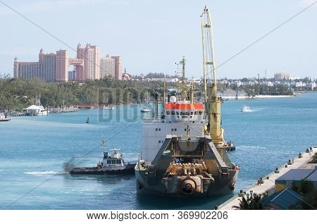 The Tugboat Pushing And Helping The Industrial Ship To Dock In Nassau (bahamas).