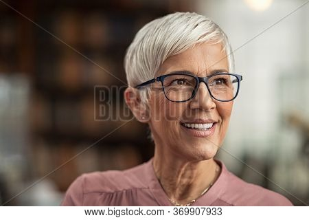 Portrait of smiling mature woman with spectacles in library looking away. Senior librarian standing in reading hall and thinking. Old beautiful lecturer contemplating. Future and vision concept.