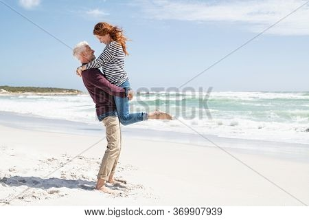Mature couple hugging on the beach with copy space. Happy wife hugging her husband at the beach with her feet off the ground. Loving senior man lifting woman above the ground hugging her.