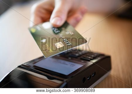 Close up hand of woman paying bill with credit card by contactless. Hand make payment with credit card with NFC technology on terminal device. Mobile payment at coffee shop with card reader machine.