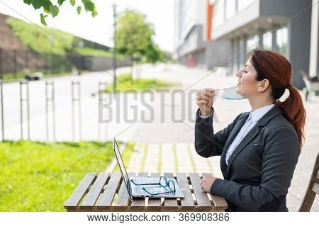 Happy Business Woman Working On A Laptop Outdoors While Maintaining A Social Distance. A Smiling Gir