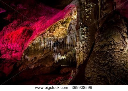 Cave With Multicolored Lighting Of Stone Stalagmites And Stalactites