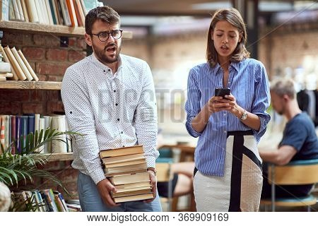 old-fashioned male carrying heavy pile of books at library, struggling. modern female watching e-books on her cell phone. books versus e-books concept