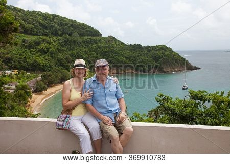 A Happy Couple Sitting On A Stone Parapet On A Clear Sunny Day Against The Backdrop Of The Beautiful