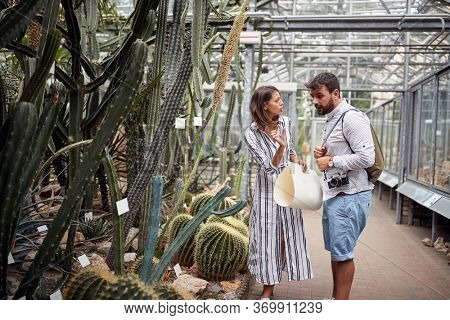 young female guide explaining details of some plants with fingers, talking, explaining to a surprised male tourist. Botanical garden.