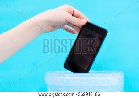Digital Detox Concept. Children's Hand Throws A Smartphone Into The Trash. Gadget Addiction
