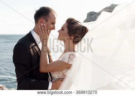 The Bride And Groom Look At Each Other On The Background Of A Magnificent View Of The Sea, Mountains