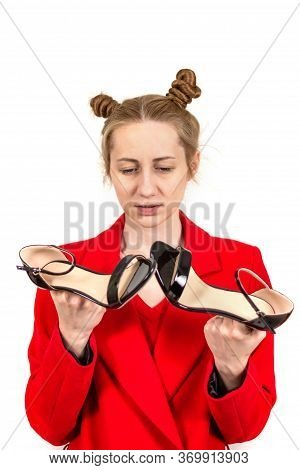 Beautiful Young Stylish Girl Disappointed, Sad Looks At The Sandals Dressed In A Red Coat In The Han