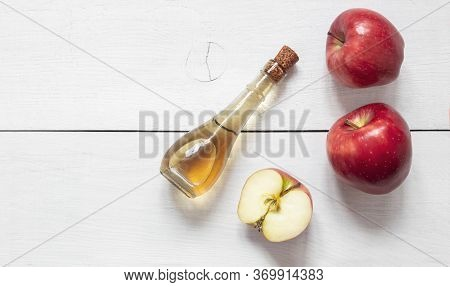 Top View Glass Bottle Of Organic Apple Cider Vinegar With Sliced And Ripe Fresh Apples On Rustic Tab