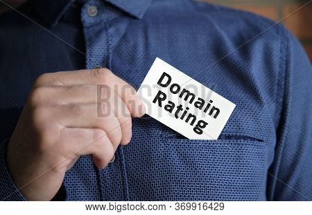 Domain Rating Text On A White Sign In The Hand Of A Man In Shirt