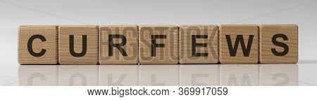 Curfews Word Text On Cube Blocks On White Gray Glossy Background With Reflection. Curfew Order Conce