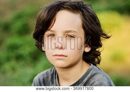 Portrait Of Thoughtful Preteen Boy With Long Hair