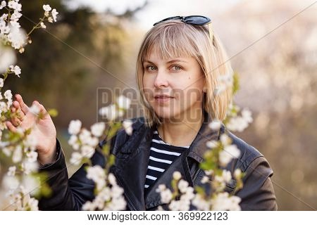 Pretty Woman With  Blond Hair Posing Near A Big Flowering Tree In A Spring Park