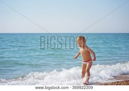 Toddler Boy Playing With Waves On The Beach