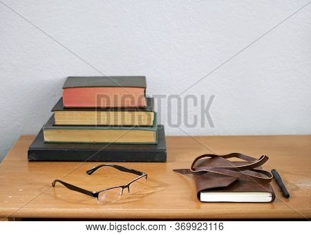 Leather Journal, Pencil, Readers, And Hardbound, Used Books Stacked On A Weathered, Used Wooden Desk