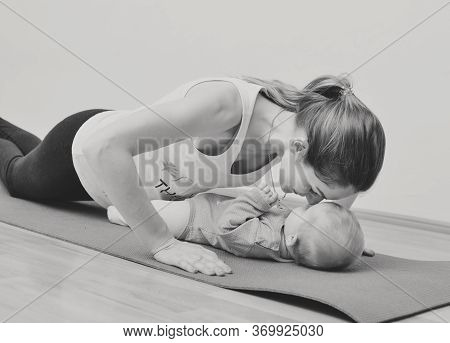 Young Mother Does Physical Yoga Exercises Together With Her Baby