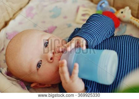 A Baby Holding Bottle And Drinking Water