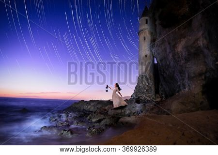 Lost Girl Looking to the Ocean With a Lantern Seeking