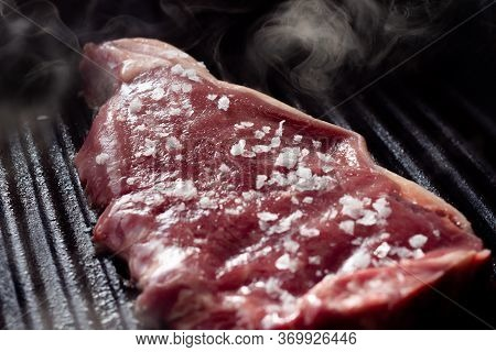 A Slice Of Sirloin Steak Frying In A Griddle Pan. The Steak Is Seasoned With Salt And Smoke Is Risin