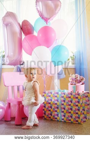 Baby Girl With Cake And Ballons In Her First Birthday