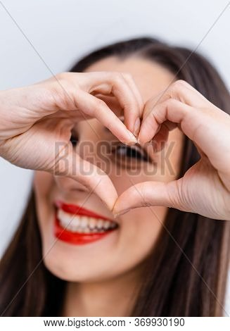 Happy Beautiful Woman Touching Fingers In Shape Of Heart And Looking At Camera. Cheerful Optimistic