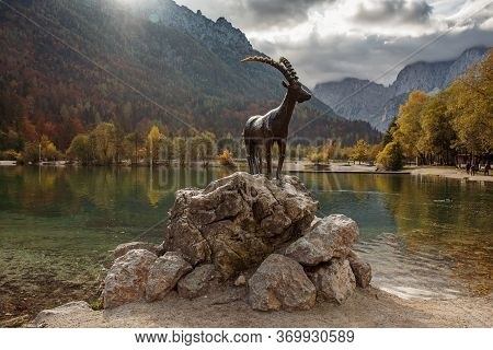 Jasna Lake With The Monument Of The Mountain Goat - Chamois Zlatorog At Front. Triglav National Park