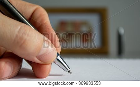 Male Hand With Metalic Pen On Beautiful White Fon On Warm Light. Wooden Picture Frame And Cap In The