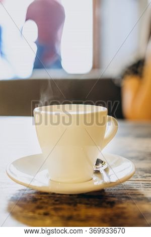 White Cup With Saucer And Small Spoon On A Wooden Table. Hot Espresso In A White Cup. Delicious Coff