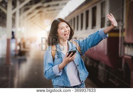 Happy Asian Woman Holding Smartphone Mobile And Waving Hand Goodbye To Farewell At Train Station Pla