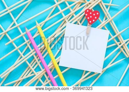 Notepaper Holding By Clothes Pin With Heart, Pencils On A Abstract Blue Background