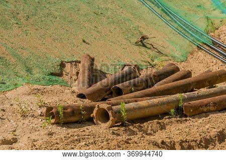 Old Discarded Iron Pipes On Sandy Ground Of New Construction Site.