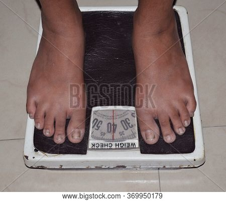 A Women Standing On Weighing Machine Or High Angle View Of Woman's Legs On Weighing Scale
