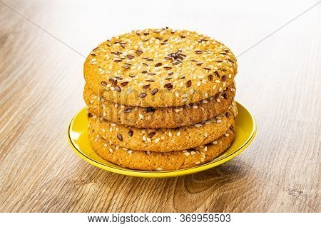 Stack Of Cookies With Sesame And Flax Seeds In Yellow Saucer On Wooden Table