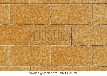 Yellow Brick Wall Made Of Symmetrical Stone Blocks With Orange And Brown Spots. Natural Pattern. Abs