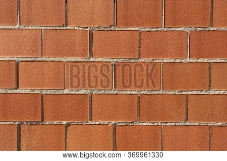 Closeup Of A Brick Wall Under The Sunlight. Abstract Red Brown Background