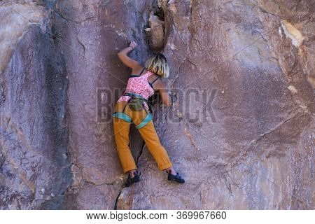 A Girl Climbs A Rock. The Athlete Trains In Nature. Woman Overcomes Difficult Climbing Route. Strong
