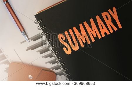 Word Summary, On Copybook Cover, Financial Report, Pen And Wallet. Business Brief Review And Conclus