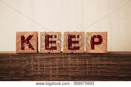 Keep Word On Wooden Cubes On A Wooden Background. Keeping Things Constant Or Keeping Money Concept.