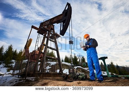 Male Worker Using Notebook Controlling Work Of Petroleum Pump Jack. Operator In Work Overalls And He