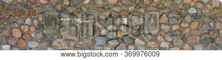 Fragment Of A Massive Wall Of An Ancient Building With Decorative Elements. Panorama Of A Stone Wall