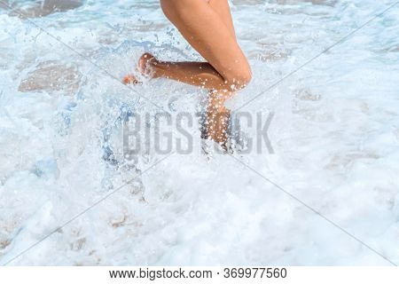 Beautiful Legs Of A Young Girl In The Ocean Foam. The Wave Rolls On The Shore And Breaks On The Legs
