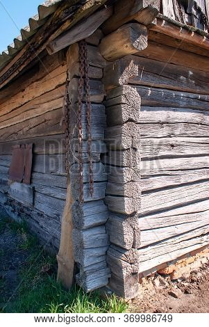 A Corner Of An Old Strong Shed. An Old, Rusty, Iron Chain Hangs On The Corner Of A Wooden House. Cor