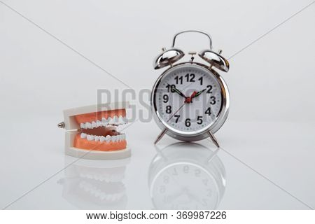 White Paper Tooth With Alarm Clock On Blue Background. Time To Dental Health. Dentist Day Concept. F