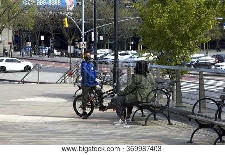 Bronx, New York/usa - April 25, 2020: Kid On Bike With Mask And Adult Nearby During Covid-19 Pandemi