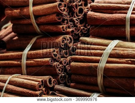 A Pile Of Bound Cinnamon Sticks Background. Asian Bazaar Seasoning Backdrop.
