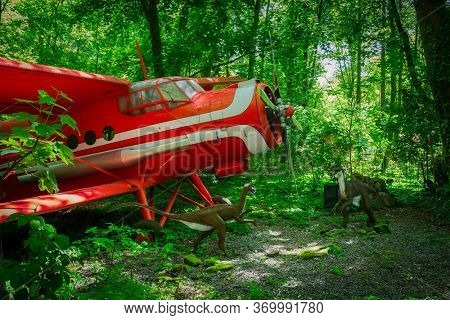 Malbork, Poland - June 1, 2020: Realistic raptor dinosaurs and red plane at the Dino Park in Malbork, Poland. Dino Park is a tourist attraction with moving dinosaurs and dragons.