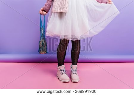 Girl In Trendy Pink Boots Plays With Long White Skirt. Photo Of Young Lady In Black Pantyhose Standi