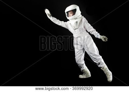Astronaut On A Black Background Goes Forward And Stretches His Hand Somewhere. Astronaut In A Spaces
