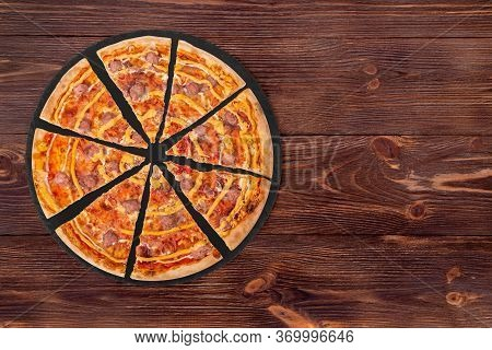 Sliced Salsiccia Pizza With Beef Sausages, Mozzarella, Various Sauces And Marinated Red Onions On A